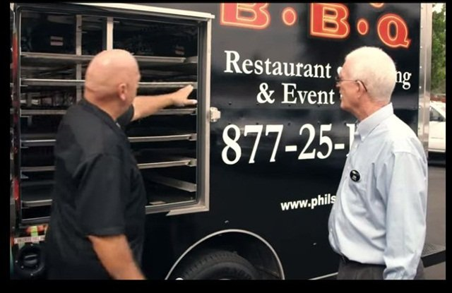 Phil Pace (left) talks with Don Hughes, his Business Elite representative, near one of his fleet vehicle's built-in oven compartment.