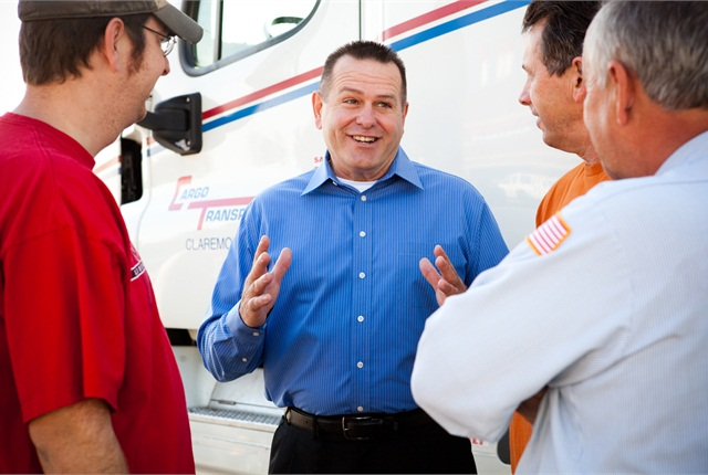 Dennis Dellinger, president of Cargo Transporters, with some of the company's drivers. The company makes use of its mobile communications and telematics technologies to improve mpg and reduce paper.