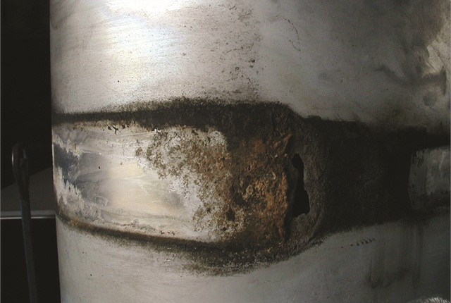 Corrosion of thisaluminum tank under its steel straps was severe enough to eat a hole into it, allowing diesel fuel to leak out.