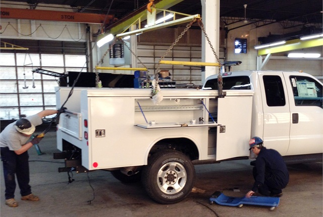 Workers at Reading Group install a utility body on a Ford SuperDuty chassis. Upfitters must meet numerous Federal Motor Vehicle Safety Standards and then certify compliance.