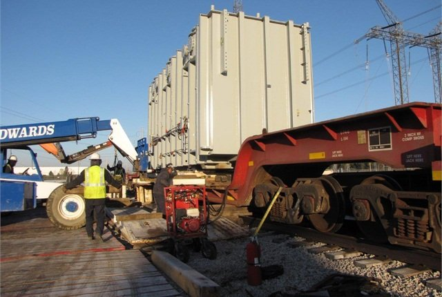 Crew uses extended-boom forklift to place rails under the load on the railcar, which has been jacked off its springs for stability.