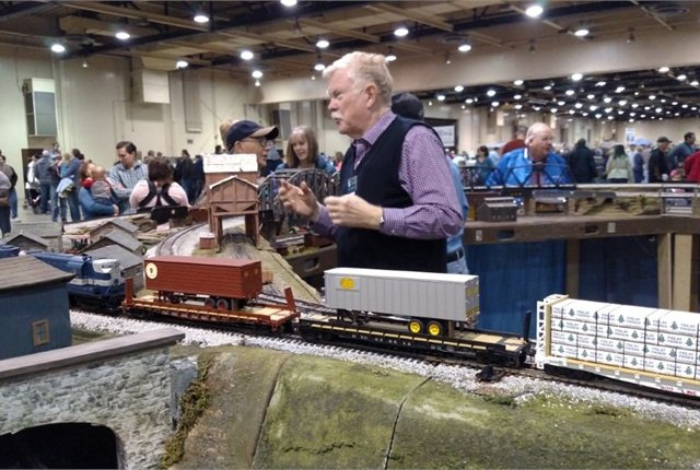 S-scale modeler Larry Robertson chats with a visitor as his freight train pauses on the tracks. Note the trailer-on-flatcar loads, an activity of progressive railroads starting in the 1950s.Photos: Tom Berg