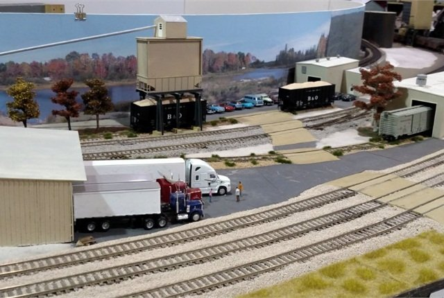 At a flooring mill, three rigs are backed against the dock while their drivers shoot the bull as theywait to load. Hopper cars (at top) will carry awaysawdust.