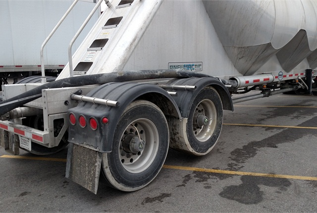 Mac trailer's forward axle is raised when the tank's empty.Note also the shroudingaround the hoppers and the stairs.