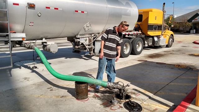 Driver Jeff McMannus checks progressas he delivers a load of biofuel through an appropriately green hose. Hewas careful to avoid spills. Photos: Tom Berg