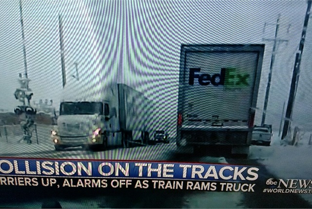 As seen from a police cruiser's dash camera, the crossing lights are dark and gates are up, and two FedEx rigs proceed across the tracks. One makes it, the other doesn't. Photos: Tom Berg
