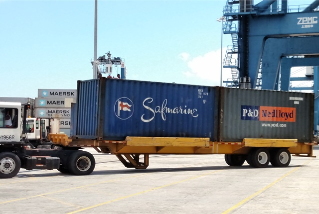 """TICO terminal tractor and shuttle chassis carry off a pair of 20-foot ocean-going containers. The trailer can also carry a single 20- and a single 40-foot """"box."""" Photo: Tom Berg"""