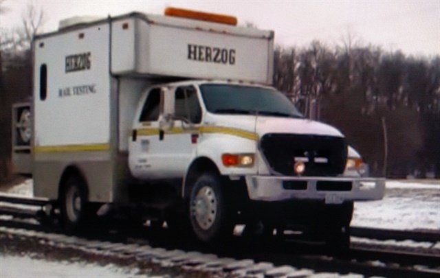 Herzog rail testing unit is mounted on a Ford F-650 or 750 chassis with a four-door crewcab.  Screen capture from YouTube.
