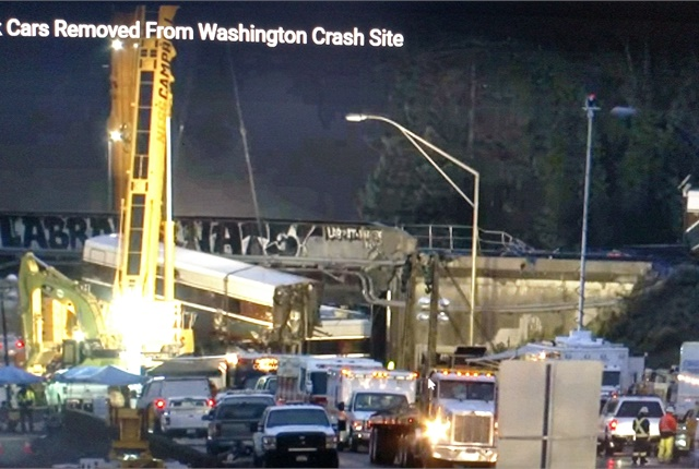 Working overnight, crews used tall cranes to loaad wreckage from the scene of the Amtrak Train 501 wreck sough of Tacoma. Screen capture from AP video