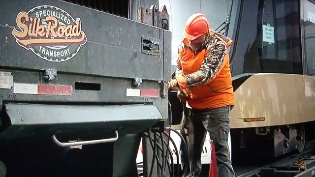 Silk Road crewman pulls out equipment to offload the 83,000-pound car onto tracks near the Amtrak station in Milwaukee.