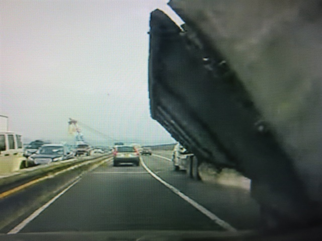 "Scrap-hauling dump trailer heels over just ahead of car in the adjacent lane on the Tappan Zee Bridge over the Hudson River. Photos: Tom Berg, from video by ""Hypotenuse"""