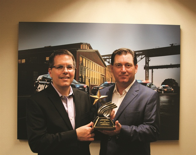 Robert Brown Jr., Great Lakes sales manager for Automotive Fleet  (right), presents the 2015 Fleet Car of the Year award to Fritz Ahadi, general manager, Commercial and Government Sales Operations at Ford Motor Co. This is the fifth win for the Ford Fusion.