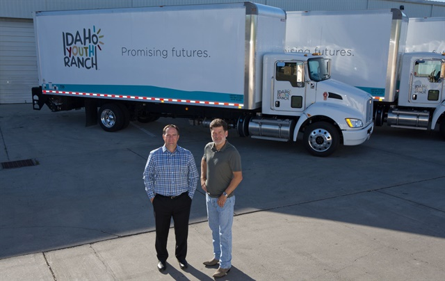 "Jamie Schaefer (left), PacLease manager at Kenworth Sales Co., has worked with Idaho Youth Ranch for several years. Through this partnership, Gregg Crow (right), IYR's former director of distribution, was able to add new trucks to help expand IYR's network of thrift stores. Crow recently stepped down, handing over the reins to Jason Whitley. ""Gregg kept feeding me information and how-to's on his job; I learned from the best,"" says Whitley."