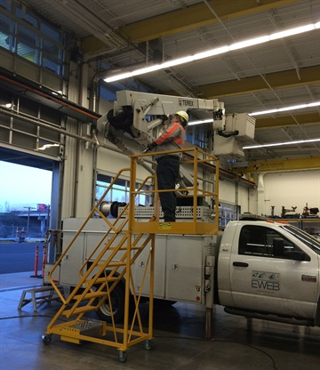 Cantilever ladders have wheels so they can be moved to whatever vehicle needs to being repaired.