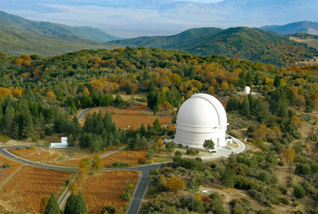 The large mirror and its telescope reside with two smaller instruments inside the dome of Palomar Observatory in northern San Diego County. Photo via Caltech
