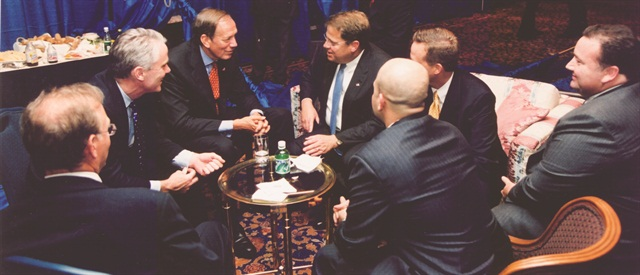 Ray Wagner of Enterprise (middle, right) presents the car rental industry's case on the CDW ban to New York Governor George Pataki (middle, left). After a 10-year battle, a bill was finally passed to overturn the law in 1999.