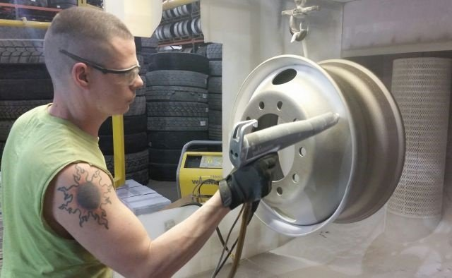 "Juan Klinehoffer, the ""wheel man"" at Bob Sumerel Tire in Zanesville, Ohio, air-sprays positively charged powder at the negatively charged wheel. There it clings until curing."