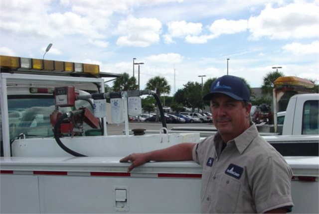 Donald (Troy) Smith, heavy equipment technician, stands beside one truck with a modified auxiliary fuel tank. Photo courtesy of Sarasota County.