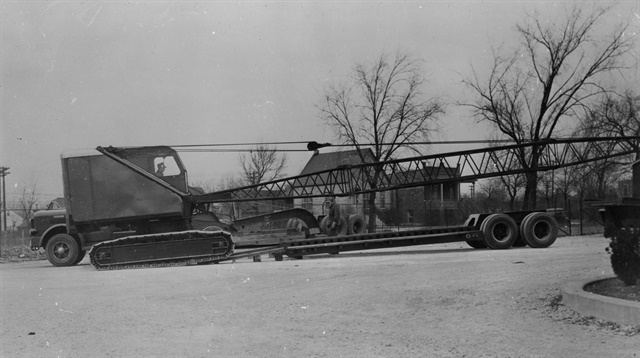 A tracked crane crawls aboard a Talbert low-bed trailer whose mechanical gooseneck nose can be seen just beyond. A second lowboy trailer sits beyond that. The long-nose tractor appears to be a Hendrickson, built by another company that, like Talbert, was based in Lyons, Illinois, west of Chicago.