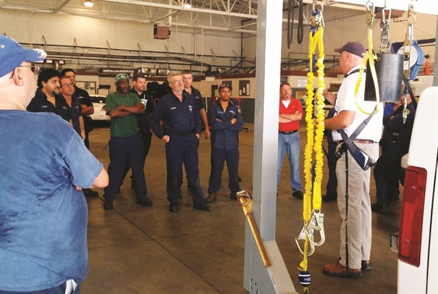 A vendor representative demonstrates various harnesses available for technicians as part of the fleet's safety program. Photo courtesy of City of Tampa