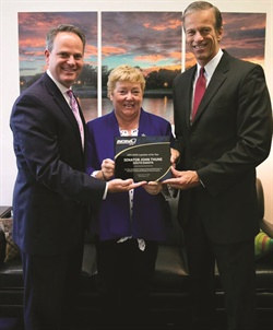 "Gordon Reel and Sharon Faulkner present Sen. John Thune (R-S.D.) (right) with one of two ACRA Legislator of the Year Awards. Thune, chairman of the Senate Commerce Committee, incorporated the car rental recall amendment into the Highway Bill during the committee process. ""Sen. Thune also worked with ACRA to ensure the provision remained in the final bill that ultimately passed and was signed into law,"" Reel said."