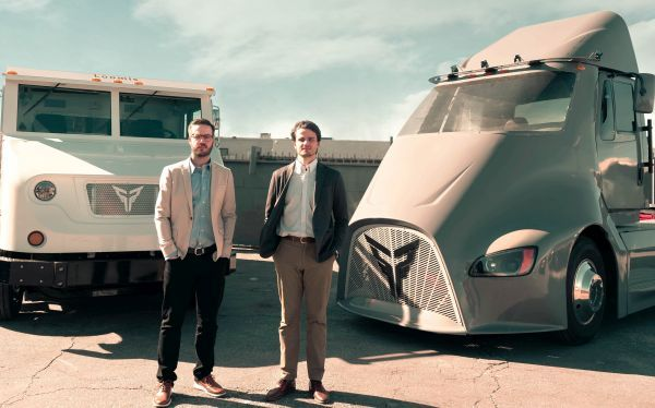 Dakota Semler (left), cofounder and CEO of Xos Trucks, stands with cofounder and COO Gio Sordoni in front of the Class 6 electric armored vehicle used by Loomis and its Class 8 tractor, ET-1. - Photo courtesy of Xos.