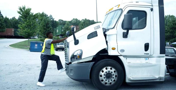 Pictured is a technician keeping his back straight while opening the hood of a truck.