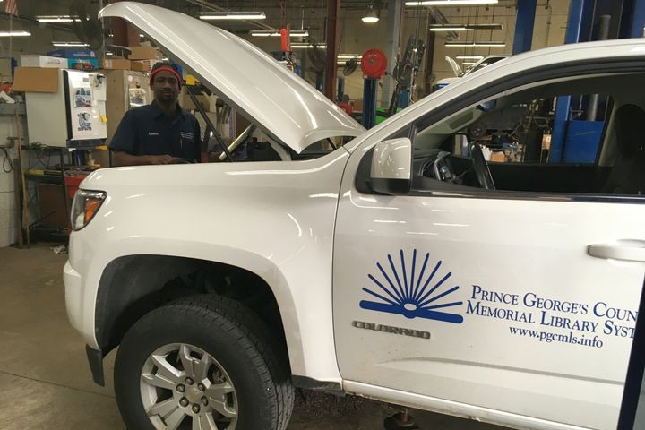 Prince George's County (Md.) technician Limbert Emmanuel is pictured working on a library system pickup truck, a new insourcing client for the county. - Photo: Prince George's County