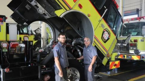 Technicians Tony Mulero and Louis Perea work on a fire truck, for which the fleet team was able...
