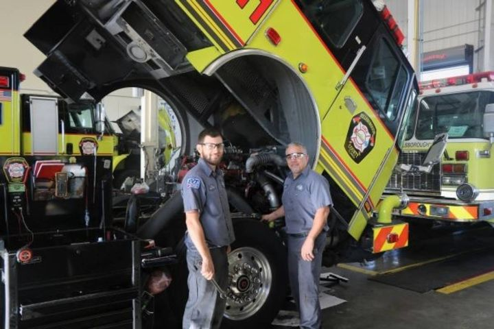 Technicians Tony Mulero and Louis Perea work on a fire truck, for which the fleet team was able to reduce procurement costs. -