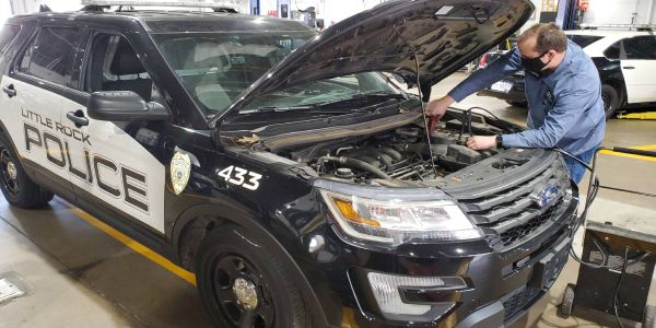 A City of Little Rock technician works on a police car.