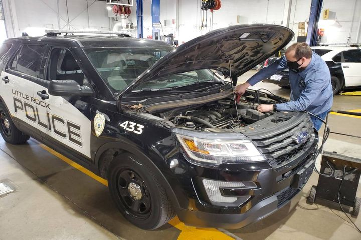A City of Little Rock technician works on a police car. - Photo: City of Little Rock