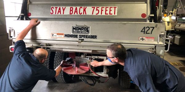 Nathan Peters and Pete Falish, both City of Green Bay, Wisconsin, mechanics, work together to...