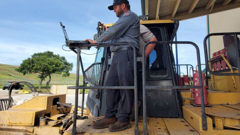 Fleet Technician Supervisor David Alligood works with another technician to diagnose a compactor...