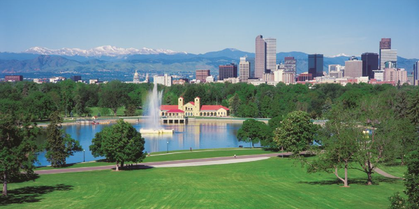 Pictured is a view of the Denver skyline from City Park, with the Rocky Mountains in the background.