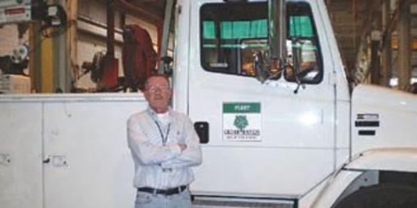 Dennis Hogan stands by a 2001 Freightliner FL 80 mechanic service truck.