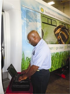 Fleet Technician Troy Smith updates software on one of the institution's hybrid-electric buses.