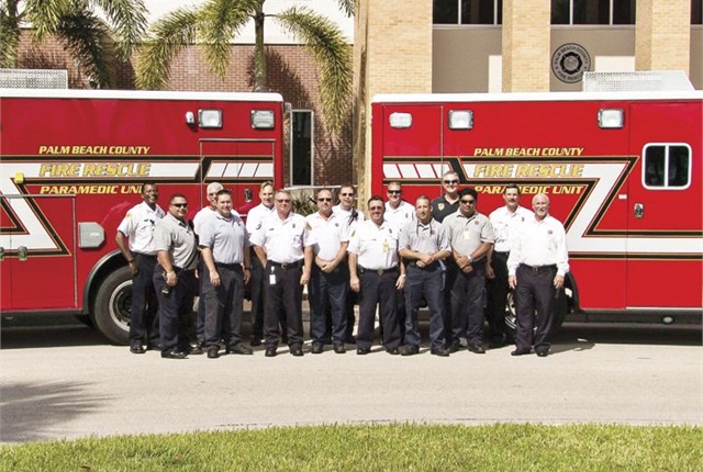 Palm Beach County (Fla.) Apparatus Committee members stand in front of two of the Fire Department's rescue trucks. Photo courtesy of PBCFR.