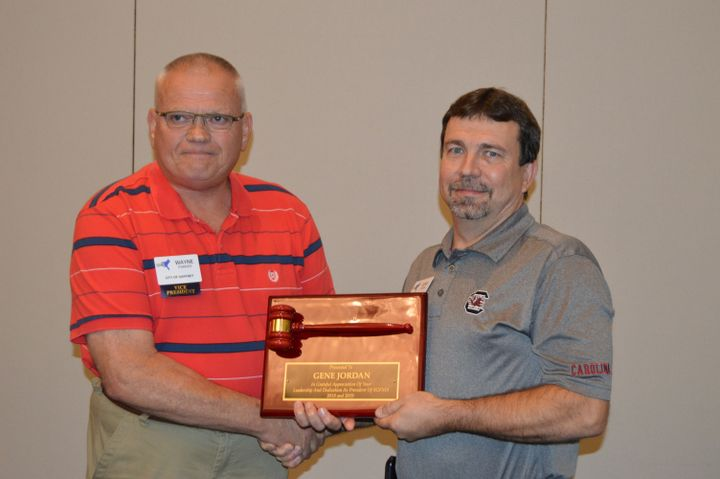New SGFMA president Wayne Parker (left) gives an award to outgoing president Gene Jordan.