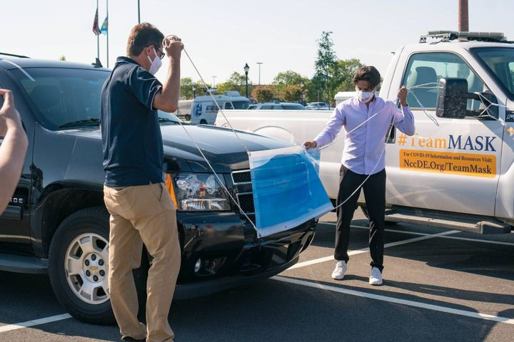Mac Macleod, CEO of Carvertise, with the help of New Castle County Executive Matt Meyer, affixes a mask on a New Castle county vehicle at their Aug. 5 launch event. - Photo: Carvertise