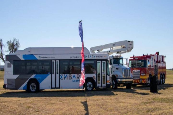 A city bus, parks cherry picker, and fire truck representing the transit, parks, and fire vehicles that will be maintained in the new facilities formed event's backdrop. - Photo: City of Norman, Okla.