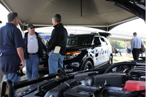 Fleet buyers discuss police vehicles at the Michigan State Police testing. Photo by Paul Clinton.