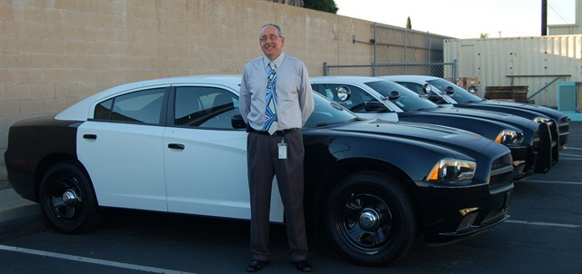 Fleet Superintendent Ron Lindsey stands in front of three new Dodge Chargers for the police fleet.
