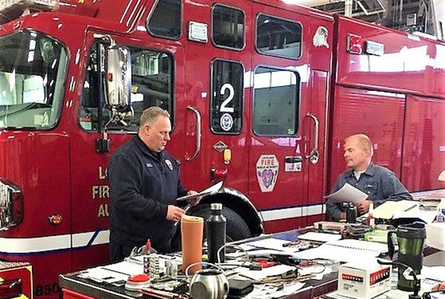 "Loveland Fire Rescue Authority Operations Division Chief Greg Ward, left, and Fleet Services Technician Corey Lane go over documentation for a truck in the ""heavy fire apparatus"" category. Photo via City of Loveland"