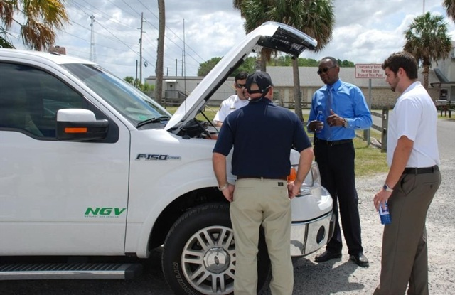 Fleet Department Director John King explains the county's CNG use while looking at a CNG-fueled vehicle. Photo courtesy of Marion County.