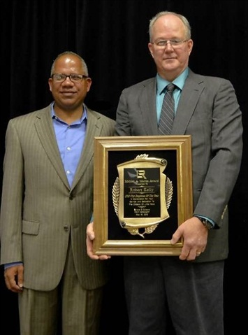 Little Rock City Manager Bruce Moore (left) and Little Rock Employee of the Year Robert Kelly (right) pose with Kelly's plaque.