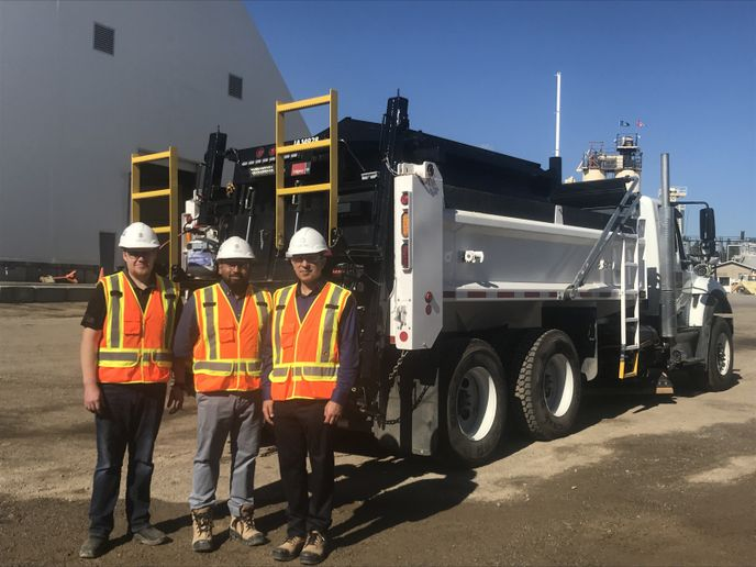 (l-r) Lucas Groening, engineering services team coordinator; Thusar Thuraisamy, acquisition specialist; and Majid Asefi, fleet operations manager, pose in front of a city vehicle