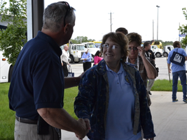bob Stanton greets attendees as they get off the bus to begin their tour.