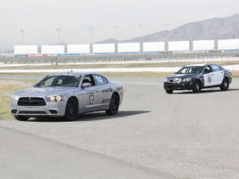 A Dodge Charger Pursuit and Chevrolet Caprice finish their test laps at the same time.