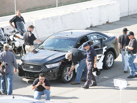 A pit crew swarms a Ford P.I. sedan following its 32 laps.